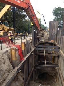 men operating crane lowering metal beam