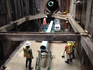 men working on underground pipe system