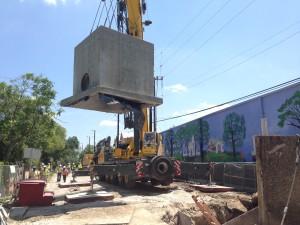 crane lowering underground pipe structure